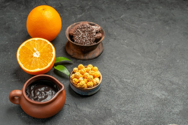 Horizontal view of set of whole and cut in half fresh oranges and biscuits on dark table
