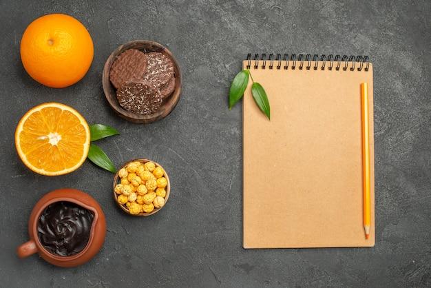 Vista orizzontale del set di arance fresche e tagliate a metà e biscotti e taccuino con la penna