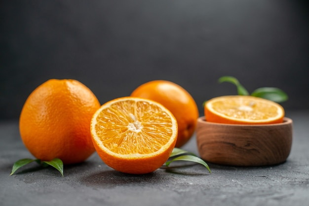 Horizontal view of set of whole and cut in half fresh oranges on dark table