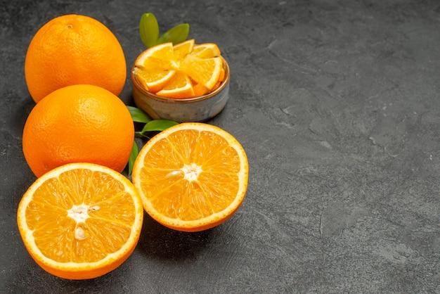 Vista orizzontale del set di arance gialle intere e tritate sul tavolo scuro