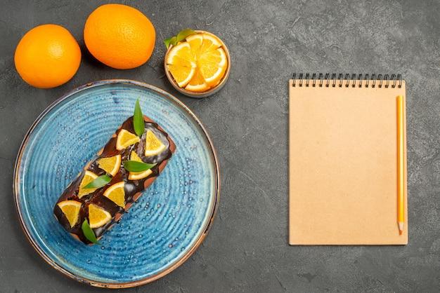 Vista orizzontale di morbida torta deliziosa e arancia accanto al notebook sulla tavola nera