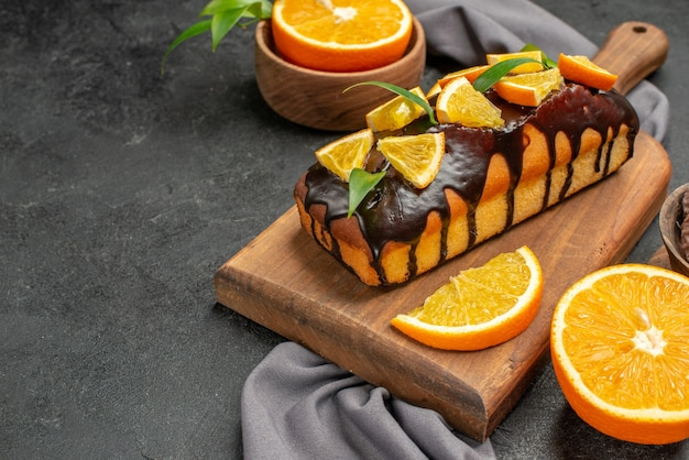 Horizontal view of soft tasty cakes cut oranges with biscuits on wooden cutting board and towel