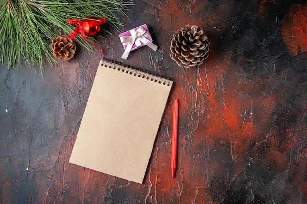 Vista orizzontale del regalo e del regalo del cono della conifera della penna del taccuino a spirale su fondo scuro