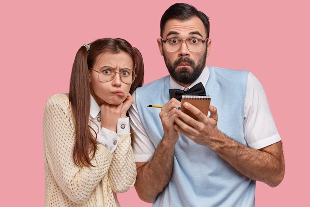 Horizontal view of surprised male geek and his beautiful girlfriend with pony tails, wears thick lenses spectacles, make records in small notepad