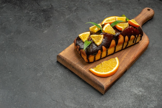 Horizontal view of tasty cakes decorated with oranges and chocolate on cutting board on black table
