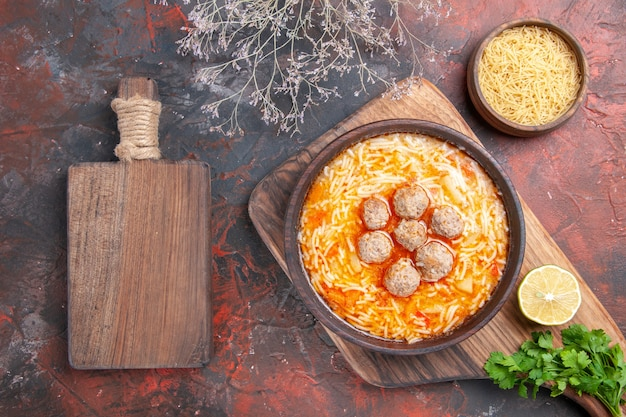 Horizontal view of tasty meatballs soup with noodles on board lemon wooden pasta a bunch of greens on dark background