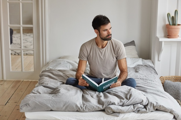 Horizontal view of thoughtful bearded man holds book, sits crossed legs on comfortable bed