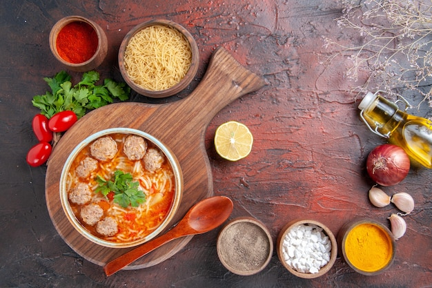 Horizontal view of tomato meatballs soup with noodles in a brown bowl and different spices oil bottle onion garlic on dark background