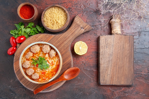 Horizontal view of tomato meatballs soup with noodles in a brown bowl different spices and wooden cutting board on dark background