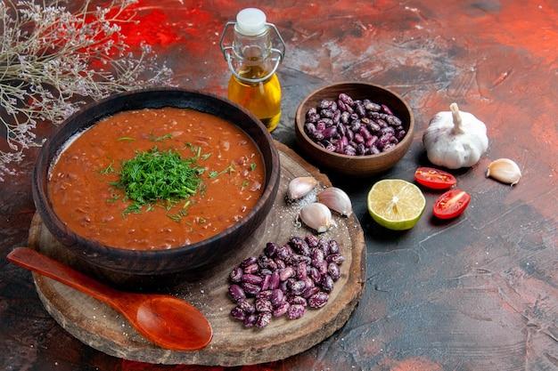 Vista orizzontale del cucchiaio di aglio di fagioli di sapone di pomodoro sul tagliere di legno e bottiglia di olio limone