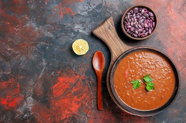 Vista orizzontale della zuppa di pomodoro fagioli caduti bottiglia di olio sul tagliere su una tabella di colori misti