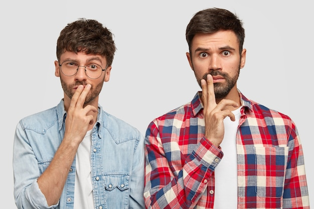 Horizontal view of two bearded male students have serious thoughtful expressions, keep fingers on mouthes, try to find solution, solve problem, work on project, wear casual clothes, stand indoor
