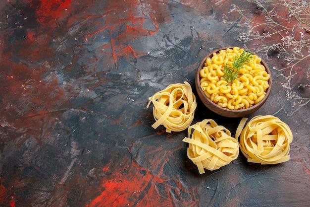 Vista orizzontale di tre porzioni crude di spaghetti e pasta a farfalla in una ciotola marrone e verde sul lato sinistro della tabella dei colori misti