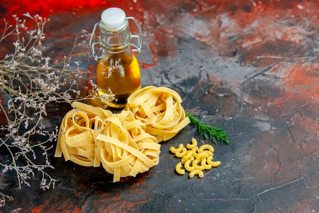 Horizontal view of uncooked three portions of spaghetti and green oil bottle on mixed color table
