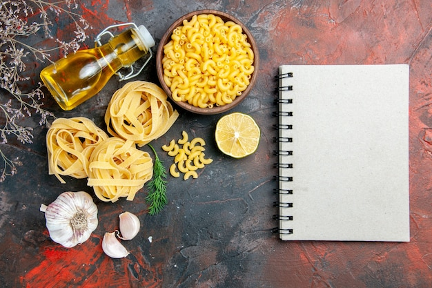 Horizontal view of uncooked three portions of spaghetti green oil bottle and notebook on mixed color table