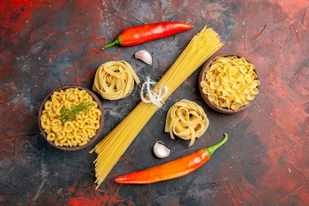 Horizontal view of various types of uncooked pastas and peppers on mixed color table
