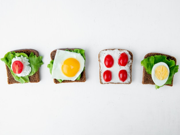 Horizontal view of vegetables as tomato egg spinach on slices of bread on white background with copy space
