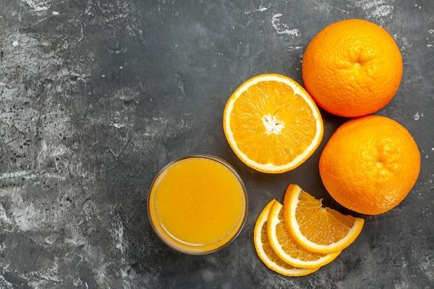 Vista orizzontale della fonte di vitamina tagliata arance e succo freschi tritati e interi su sfondo grigio