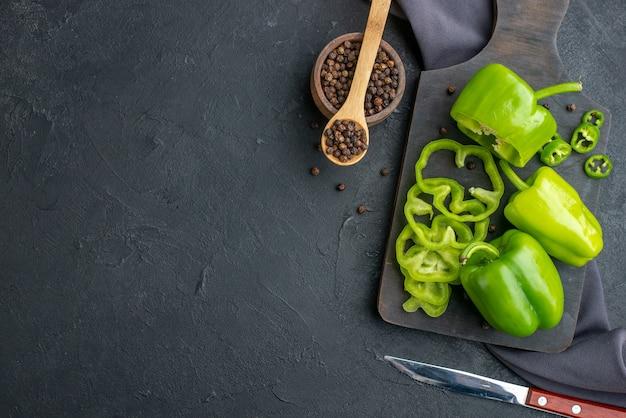 Vista orizzontale di peperoni verdi tagliati interi tagliati su tagliere di legno su superficie di colore scuro