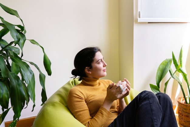 Horizontal view of woman at home holding a cup of tea sit on a green pouf.