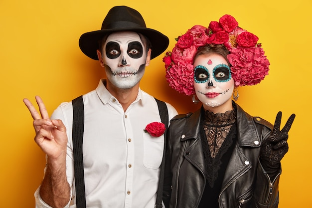 Horizontal view of woman and man wear bright makeup, make peace gesture, wear traditional clothes, celebrate dead of death, isolated over yellow background.