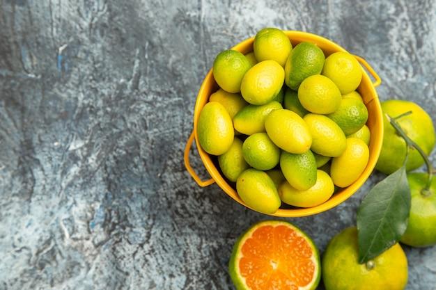Vista orizzontale di un secchio giallo pieno di mandarini verdi freschi e tagliato a metà mandarini sul lato destro dello sfondo grigio
