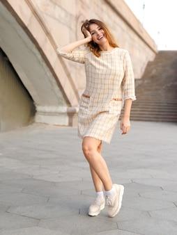 Горизонтальный вид. молодая привлекательная женщина с рыжими волосами, носить бежевое элегантное платье, позирует на улице. красивая девушка гуляет по улице.