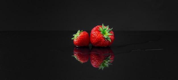 Un colpo grandangolare orizzontale di due fragole rosse su una superficie riflettente nera