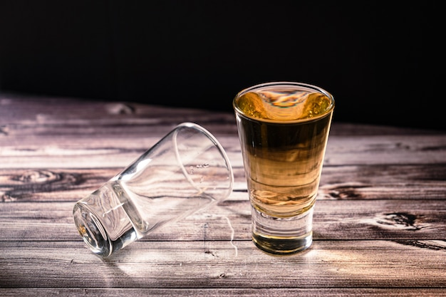Horizontally oriented chopped view of a shot of whiskey or scotch or bourbon next to a second dropped shot.