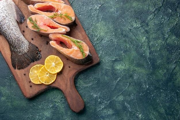 Горизонтальный вид свежей сырой рыбы, ломтиков лимона, зелени, перца на деревянной разделочной доске на столе темных цветов