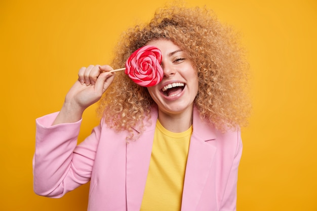 Horizotal shot of curly happy woman covers eye with tasty sweet candy has fun laughs happily dressed in formal clothes isolated over vivid yellow wall. lovely glad female holds lollipop
