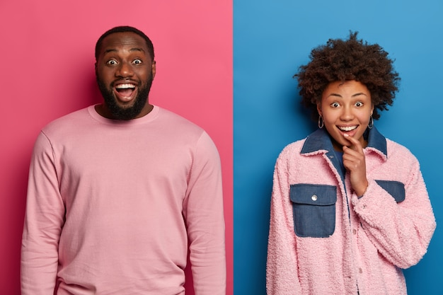 Horizotal shot of happy curious woman and man have dark skin look with interest and shock, react to awesome news, gasp from excitement, left speechless from cute present, stand over two colored wall