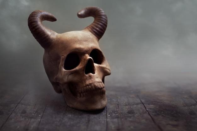 霧の中で角のある人間の頭蓋骨。ハロウィーンのテーマ、コピースペース。