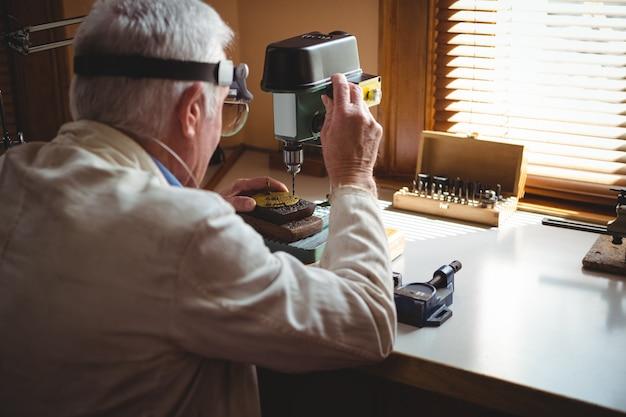 時計職人が文字盤を穴あけ