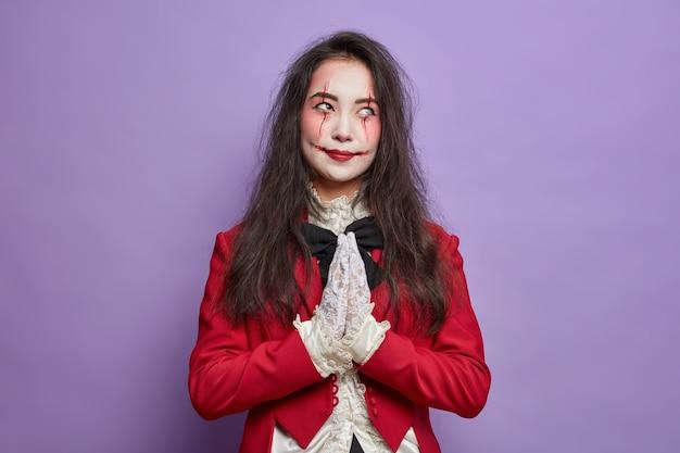 피 묻은 흉터를 가진 끔찍한 여성 좀비는 할로윈 축제 메이크업을 착용하고 손바닥을 함께 누르고 의상을 입고 보라색 벽에 고립 된 좋은 것을 믿습니다.