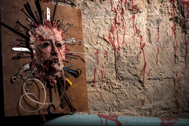 Horrible skinned bloody face of a person stretched open on a wooden board with assorted sharp weapons alongside a blood splattered wall in a halloween horror concept