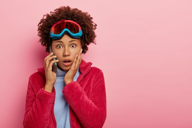 Horrified curly woman with dark skin, gets shocking news via smartphone, has worried conversation, recreats in mountains, enjoys hobby, wears ski mask, stares speechless dressed in warm winter clothes