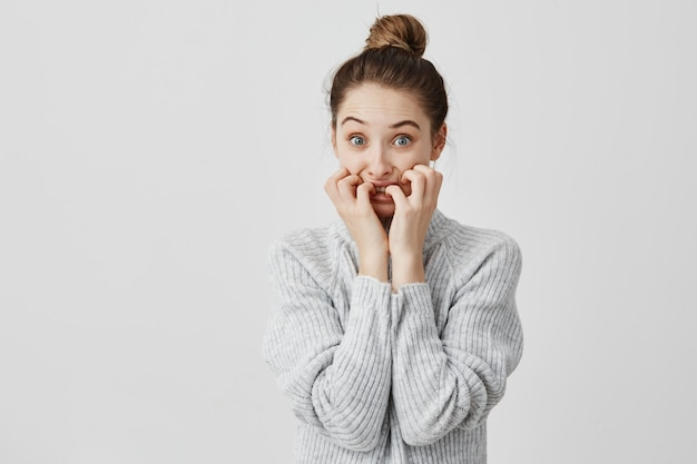 Horrified woman wearing hair in topknot looking scared biting her nails in stress. female sales manager being in trouble expressing negative emotions. horror and fear concept