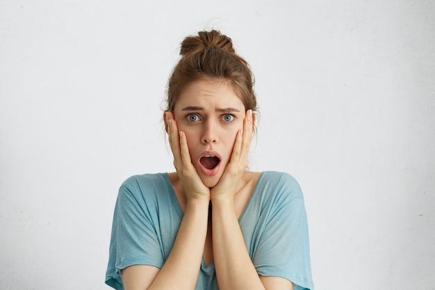 Donna inorridita con aspetto attraente che sembra spaventata tenendo la bocca aperta