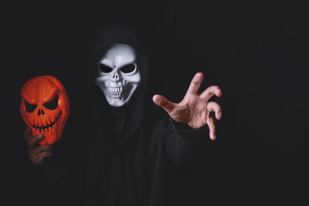 Horror devil costume with spooky pumpkin skull in black dressed for halloween carnival