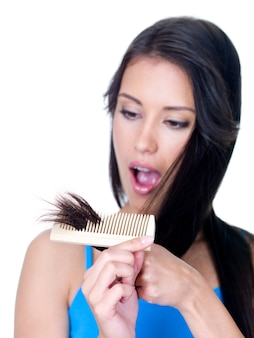 Horror on the face of young woman looking at the unhealthy ends of hair - isolated