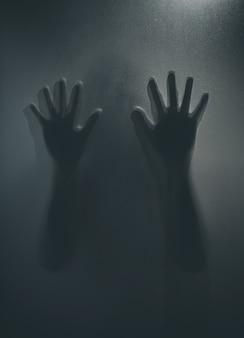 Девушка-призрак ужаса за матовым стеклом в черно-белом цвете. концепция фестиваля хэллоуина.