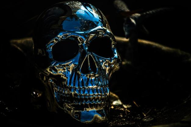 Horror halloween background. metallic human skull on black.