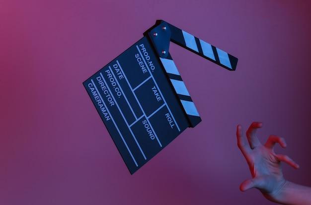 Ужас, хэллоуин. доска с хлопушкой для рук и пленки в синем красном неоновом свете. киноиндустрия, развлечения. концепт-арт, минимализм