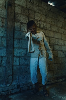 Horror for halloween holiday crazy man in a dirty measuring shirt in an old ruined house is locked and scares everyone surrounding expecting a victim