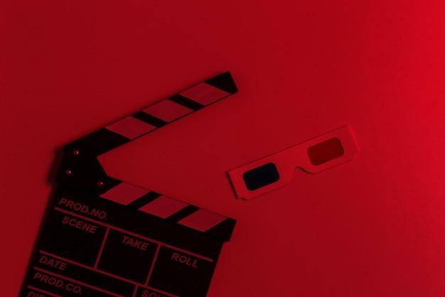 Фильм ужасов. доска с хлопушкой пленки с 3d-очками в красном неоновом свете. вид сверху
