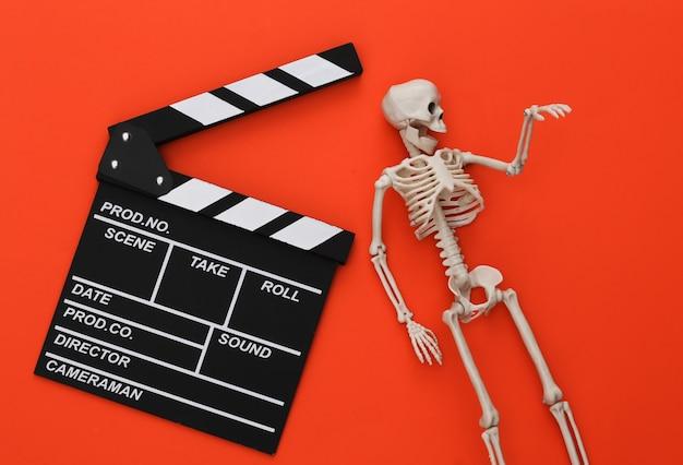 ホラー映画、ハロウィーンのテーマ。映画のカチンコとオレンジ色の装飾的なスケルトン