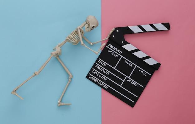 공포 영화, 할로윈 테마. 핑크 블루 파스텔에 영화 clapperboard와 장식 해골
