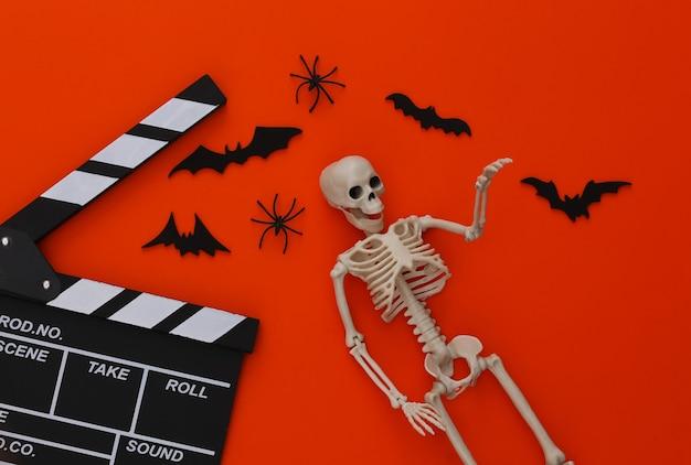 ホラー映画、ハロウィーンのテーマ。映画のカチンコ、スケルトン、クモ、オレンジ色の飛行装飾コウモリ