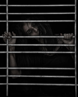 Horror scene of a possessed woman ghost halloween in dark cage pound room